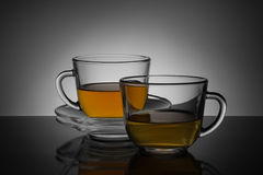 Two glass cup with tea and saucer on a black and white backgroun Royalty Free Stock Image