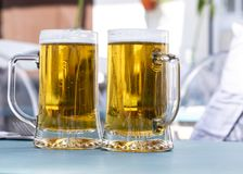 Two glass cups of a beer stock image
