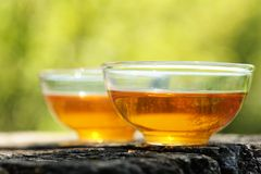 Two glass cups of black tea  on old wooden board in bright sunli Royalty Free Stock Image