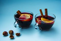 Two glass cups of mulled wine with nuts on a bright blue background. Stock Photos