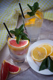 Two glass cups of water with red orange, lemon, mint and ice. Fr Royalty Free Stock Photos