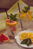 Two glass cups of water with red orange, lemon, mint and ice. Fr Stock Photography