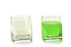 Two glass cups withgreen liquid on a white background. Two glass cups with green liquid on a white background: almost empty and the almost complete Royalty Free Stock Photo