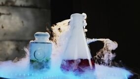 Two glass flasks on the table with illumination. Scientific experiment. White steam going from glass flask after chemical reaction. Frozen Co2 and hot water stock video footage