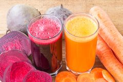 Two glass of fresh beet and carrot juice, beetroot and carrots vegetable on wooden table. Stock Photo