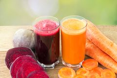 Two glass of fresh beet and carrot juice, beetroot and carrots vegetable on wooden table, defocused, nature background. Two glass of fresh beet and carrot juice Royalty Free Stock Image