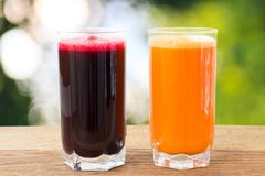 Two glass of fresh beet and carrot juice on wooden table, defocused, nature background. Two glass of fresh beet and carrot juice on wooden table, defocused Stock Photos