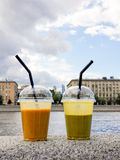 Two glass of fresh smoothie on city embankment - mango and banan stock photography