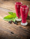 Two glass glasses with black currant smoothie royalty free stock images