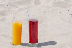 Two glass glasses with juice of mango and cherry with tubules. Sandy beach on a summer day stock photo
