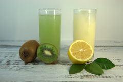 Two glass glasses with a refreshing juice and ice, on a textile stand, whole and sliced half of an orange with leaves and kiwi, stock photo