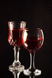 Two glass glasses with wine against a dark background. Stock Image