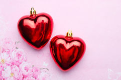 Two glass hearts on pink background stock images