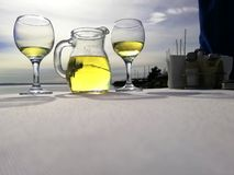 Two glass and jag with white wine on the table near the sea stock photo