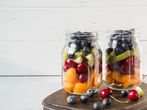 Two glass jars with berries and fruits. Fruit salad with apricots, kiwi, cherries and blueberries in glass jars on white. Background. Summer seasonal tasty stock photography
