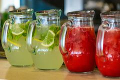 Two glass jars of home made fresh raspberry lemonade or virgin mojito cocktail with a straw on the table. Close up Stock Image