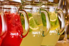 Two glass jars of home made fresh raspberry lemonade or virgin mojito cocktail with a straw on the table. Close up Stock Photo