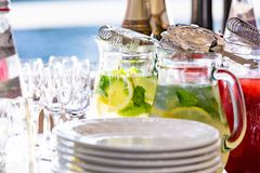 Two glass jars of home made fresh raspberry lemonade or virgin mojito cocktail with a straw on the table among dishes. Two glass jars of home made fresh Stock Photos