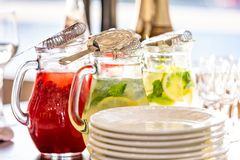 Two glass jars of home made fresh raspberry lemonade or virgin mojito cocktail with a straw on the table among dishes. Two glass jars of home made fresh Stock Images
