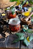 Two glass jars with homemade canned plums jam, marmalade, jelly on rustic wooden table with cardamon, cinnamon,  anise, plums stock images