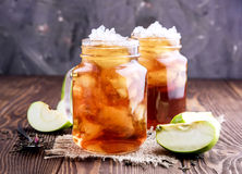 Two glass jars with iced tea on rustic background Stock Images
