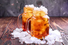 Two glass jars with iced tea on rustic background Royalty Free Stock Photos