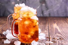 Two glass jars with iced tea on rustic background Royalty Free Stock Images