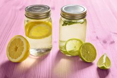 Citrus sodas with pieces of fruit on pink wood. Two glass jars with lid, one with cold water and slices of lemon and another with slices of lime and mint, are Royalty Free Stock Image