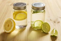 Lemon and lime soft drinks with pieces of citrus. Two glass jars with lid, one with cold water and slices of lemon and another with slices of lime and mint, are Royalty Free Stock Photo