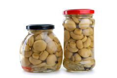 Two glass jars with marinated champignons Royalty Free Stock Images