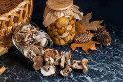 Two glass jars with wild mushrooms on black marble background. Stock Photos