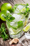Two glass of mojito cocktail with fresh lime. And mint on a wooden background Royalty Free Stock Photography