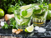 Two glass of mojito cocktail with fresh lime. And mint on a wooden background Stock Images