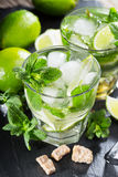 Two glass of mojito cocktail with fresh lime and mint. On a wooden background Royalty Free Stock Photo