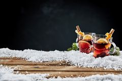Two glass mugs of hot spicy mulled red wine. Two glass mugs of traditional Christmas hot spicy mulled red wine, or Gluhwein, standing in winter snow on wooden Stock Image