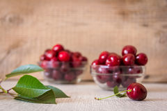 Two glass plates with cherries on the table Stock Image