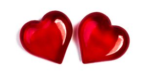 Two glass red hearts. Isolated on a white background stock image