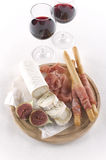 Two glass of red wine and snacks. Red wine, goat cheese, parma ham, bread sticks on white background Royalty Free Stock Images