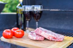 Two glass of red wine, steak and tomatoes on barbecue outdoors Royalty Free Stock Photo