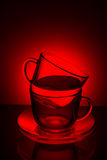 Two glass transparent cup with tea and saucer on a red backgroun Stock Images