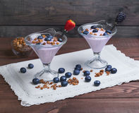 two glass vases decorated with berries and granola yogurt Stock Images