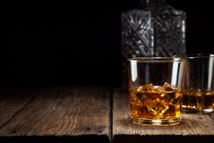 Two glass of whiskey with ice and crystal decanter on wooden table royalty free stock photo