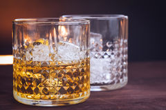 Two glass of whiskey with ice cubes on wood table, warm atmosphere Royalty Free Stock Photography