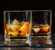 Two glass of whisky. With ice on a black background Stock Photos