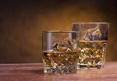 Two glass of whisky. On a wooden table Royalty Free Stock Images