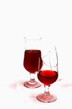Two glass with wine. Two glasses with wine and drops ,isolated on white background .one  glass is broken Stock Image