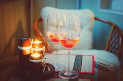 Two glass wine glasses with alcohol and lighted candles. royalty free stock photos