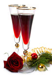 Two glasses 2. Two glasses with red wine near branch of christmas tree and decorations and red rose stock photography