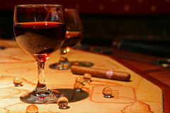 Two glasses. A closeup view of two glasses filled with red wine and cognac, cigar and glass balls on the table stock image