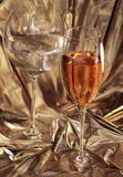 Two glasses. One glass with water, and the second with wine. Glasses stand on a gold background Stock Images